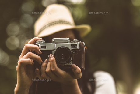Brunette in straw hat taking pictureの写真素材 [FYI00003823]
