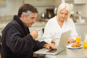 Mature couple having breakfast together man using laptopの写真素材 [FYI00003826]