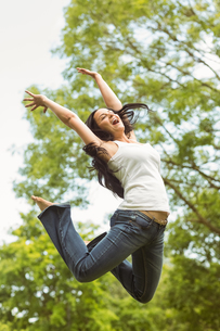 Excited brunette jumping in the parkの写真素材 [FYI00003828]