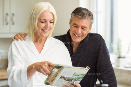 Mature couple reading magazine together in morningの写真素材 [FYI00003833]