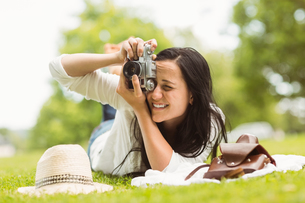 Happy brunette lying on grass taking pictureの写真素材 [FYI00003834]