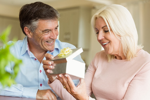 Happy mature man offering wife a giftの写真素材 [FYI00003845]