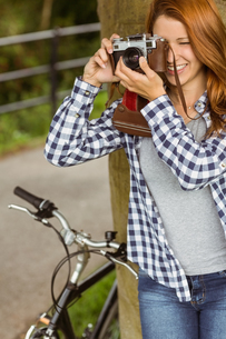 Young redhead taking a picture leaning against a treeの写真素材 [FYI00003849]