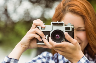 Pretty redhead taking a picture with retro cameraの写真素材 [FYI00003850]