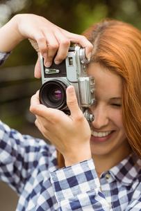 Pretty redhead taking a picture with retro cameraの写真素材 [FYI00003854]