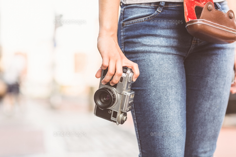 Close up of a girl wearing jean and holding a cameraの素材 [FYI00003862]