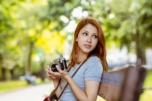 Redhead sitting on bench using her cameraの写真素材 [FYI00003863]