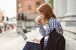 Woman drinking coffee and using laptop outsideの写真素材 [FYI00003865]