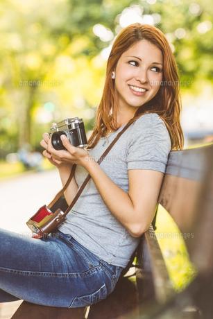 Redhead sitting on bench using her cameraの写真素材 [FYI00003872]