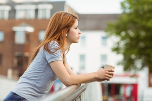 Woman with coffee cup day dreaming on the bridgeの写真素材 [FYI00003878]