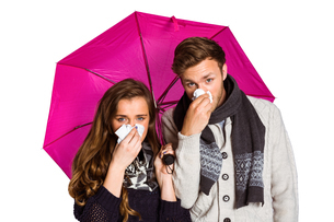 Couple blowing nose while holding umbrellaの写真素材 [FYI00003882]