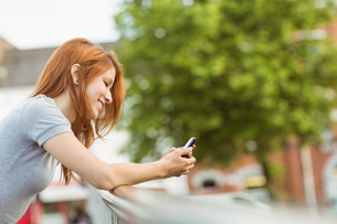 Cheerful redhead with her mobile phone texting a messageの写真素材 [FYI00003886]