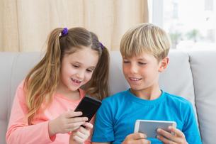 Happy siblings using smartphones on sofaの写真素材 [FYI00003921]