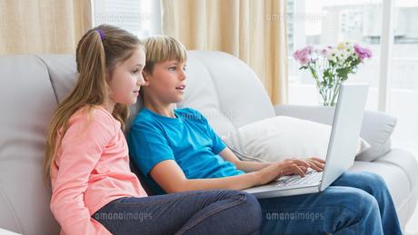 Happy siblings using laptop on sofaの写真素材 [FYI00003925]