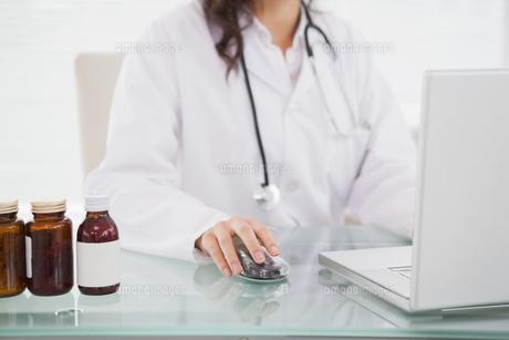 Doctor using laptop near pill bottlesの写真素材 [FYI00003943]