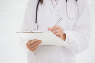 Doctor writing on clipboardの写真素材 [FYI00003947]