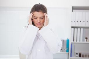 Brunette doctor suffering of headacheの写真素材 [FYI00003950]