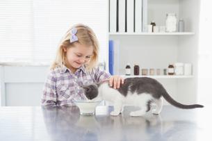 Happy owner petting her cat drinking milkの写真素材 [FYI00003957]