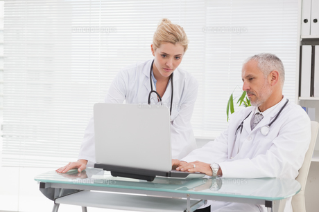 Concentrated doctors coworker using laptopの写真素材 [FYI00003986]