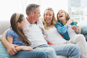 Smiling parents and children sitting together on couchの写真素材 [FYI00003997]