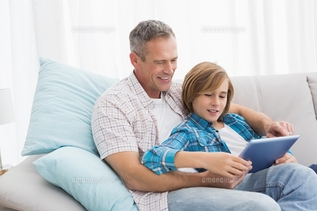 Father with son relaxing on the couch using laptopの写真素材 [FYI00003998]