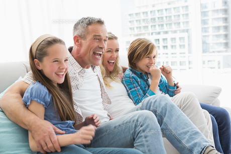 Excited family watching television on sofaの写真素材 [FYI00004003]
