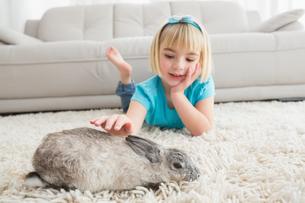 Little girl lying on rug stroking the rabbitの写真素材 [FYI00004016]