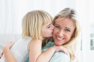 Mother sitting on the couch with her daughter kissing her cheekの写真素材 [FYI00004017]