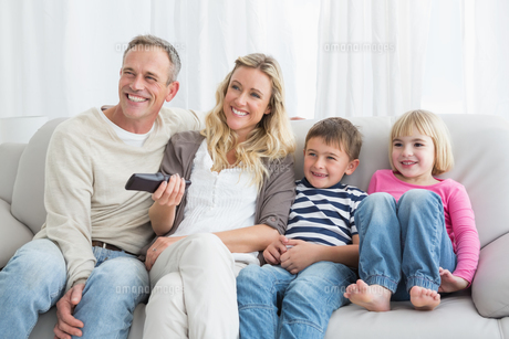 Smiling family sitting on sofa changing tv channelの写真素材 [FYI00004019]