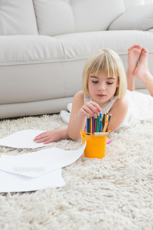 Smiling litlle girl drawing lying on the floorの写真素材 [FYI00004020]