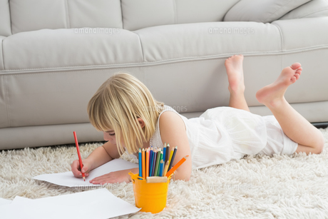 Smiling litlle girl drawing lying on the floorの写真素材 [FYI00004021]