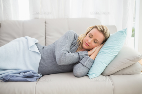 Casual pretty blonde lying on couch sleepingの写真素材 [FYI00004022]