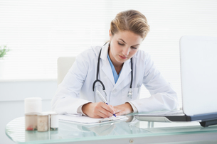 Doctor filling out prescriptionsの写真素材 [FYI00004068]