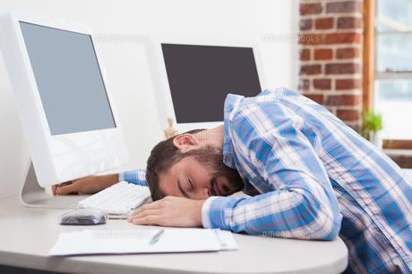 Casual businessman sleeping at his deskの写真素材 [FYI00004113]