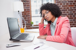 Stressed casual businesswoman sitting at deskの写真素材 [FYI00004115]