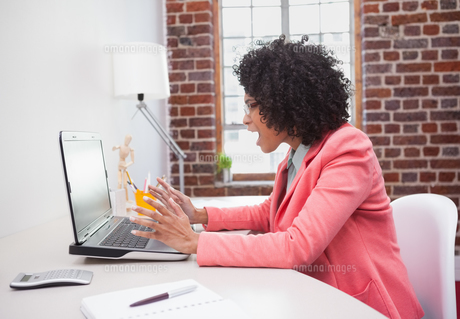 Stressed casual businesswoman sitting at deskの写真素材 [FYI00004120]