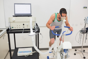 Man doing fitness test on exercise bikeの写真素材 [FYI00004130]