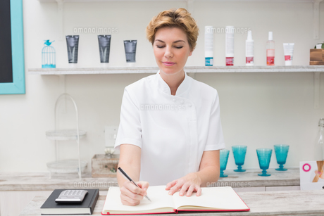 Pretty beautician writing in appointment bookの素材 [FYI00004163]