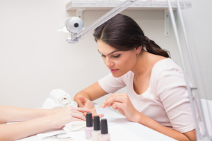 Nail technician giving customer a manicureの写真素材 [FYI00004172]