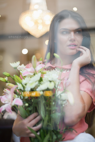 Pretty brunette holding bunch of flowersの写真素材 [FYI00004178]