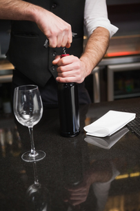 Handsome waiter opening a bottle of red wineの写真素材 [FYI00004245]