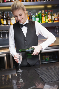 Cute woman in suit pouring champagne into fluteの写真素材 [FYI00004246]