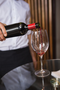 Waiter pouring a bottle of red wineの写真素材 [FYI00004254]