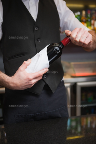 Handsome waiter opening a bottle of red wineの写真素材 [FYI00004255]