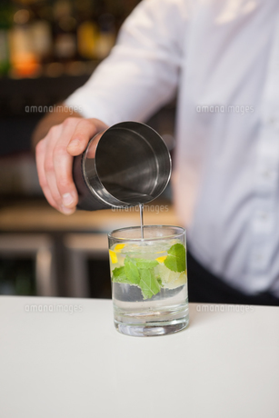 Bartender pouring cocktail into glassの写真素材 [FYI00004258]