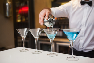 Bartender pouring blue alcohol into cocktail glassの写真素材 [FYI00004262]
