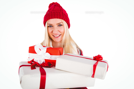 Festive blonde holding pile of giftsの写真素材 [FYI00004265]