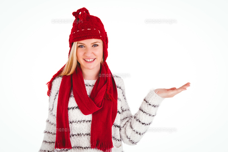 Festive blonde presenting with handの写真素材 [FYI00004269]