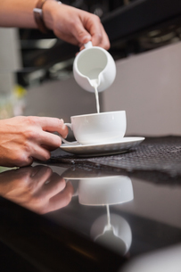 Barista pouring milk into cup of coffeeの写真素材 [FYI00004272]