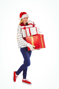 Festive blonde holding pile of giftsの写真素材 [FYI00004274]